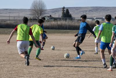 Jacks players run a passing drill at the start of practice on March 12