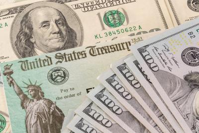 Stack Of 100 Dollar Bills With Illustrative Coronavirus Stimulus Payment Check To Show The Virus Sti