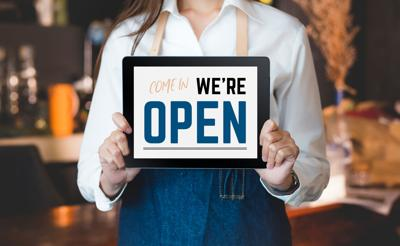 Woman Barista Wear Jean Apron Holding Come In We Are Open Sign On Tablet To Customer At Bar Counter