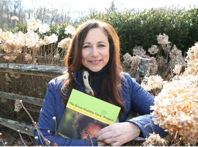 """Diane Lewis with a copy of her book, """"The Great Healthy Yard Project."""""""