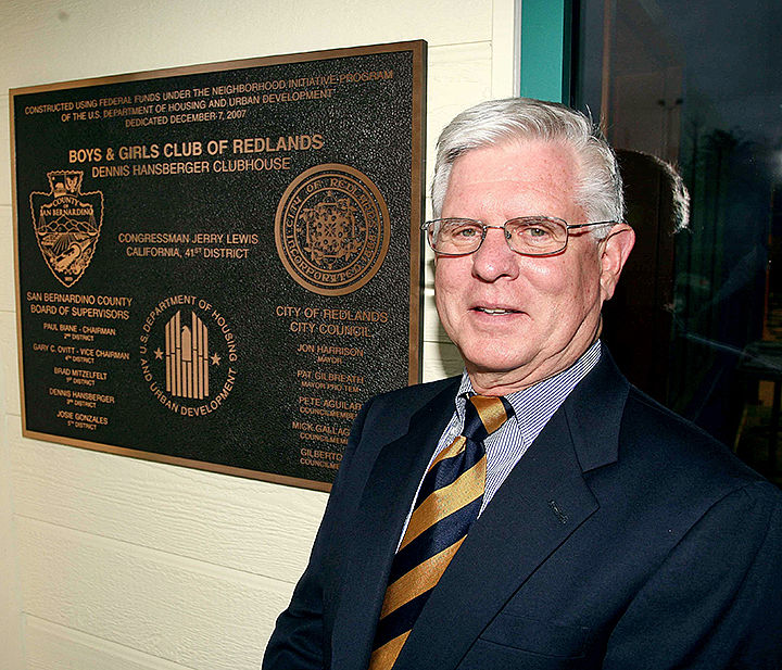 Supervisor Dennis Hansberger poses next tp a plaque outside the Hansberger Clubhouse.