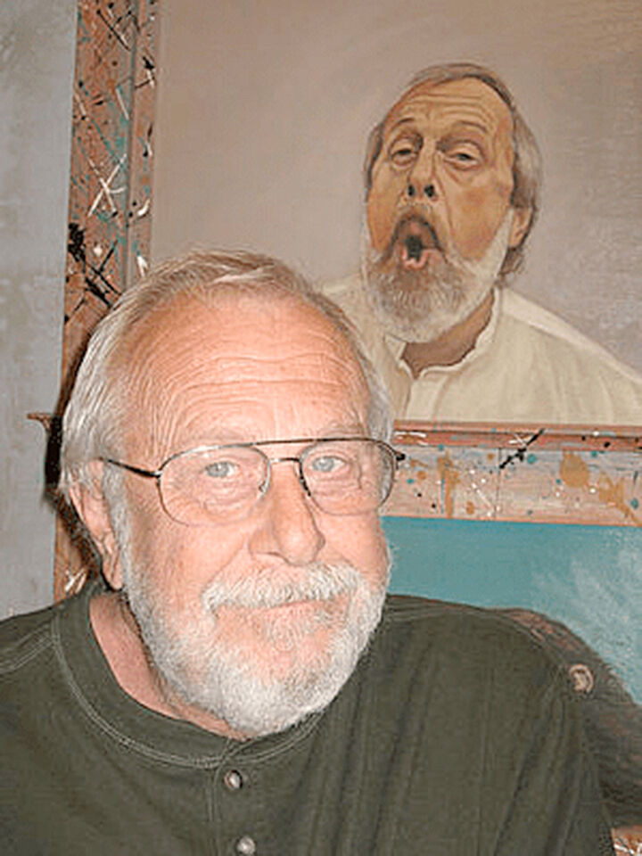 John Brownfield next to a self-portrait at the Redlands Art Association.