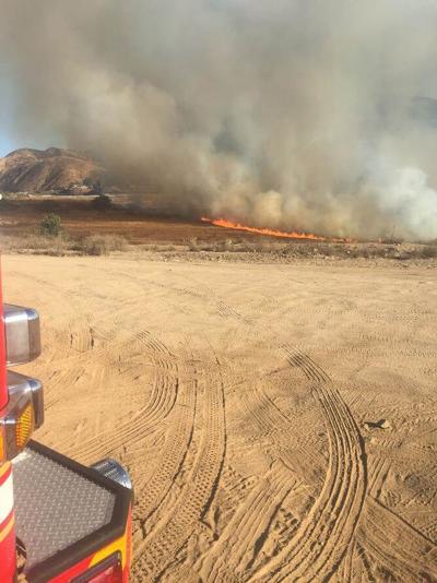 Burning vehicle starts fire.
