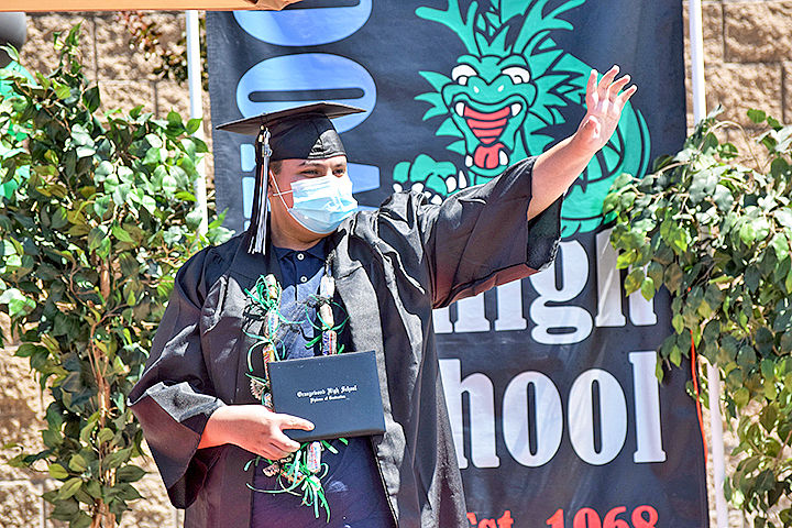 A graduate waves to his family