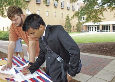MSU students Clint Kelly (left) and Navraj Batra sign up at a voter registration drive held Wednesday.