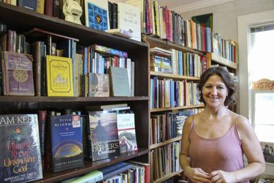 Lara Hammond stands with some of the books available for purchase in her new shop.