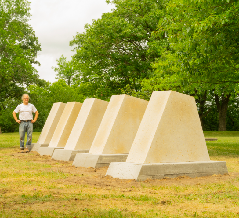 """Sculptor Pete Driessen stands by his piece titled """"Wind Dam."""""""