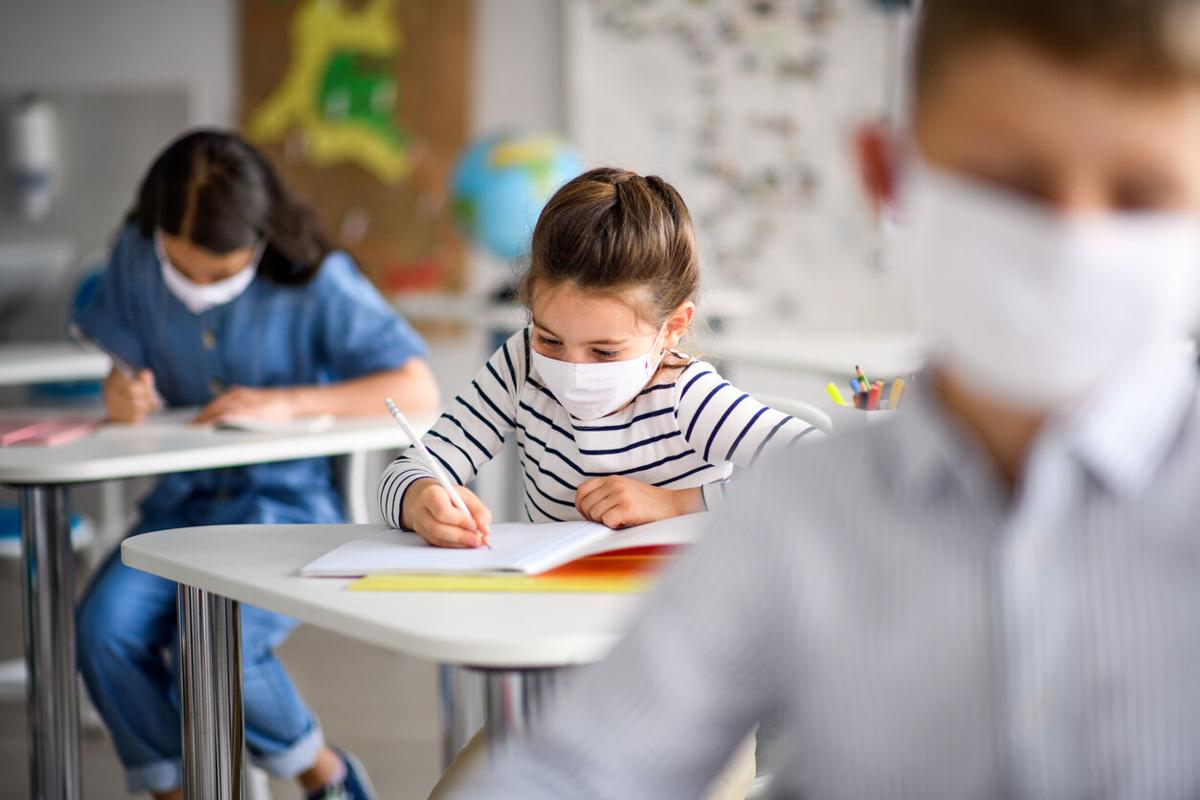 Children with face mask back at school after covid-19 quarantine and lockdown