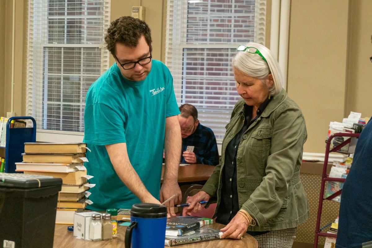 Anne Rhodes helps resident find a book