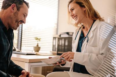 Female doctor showing good test results to a male patient