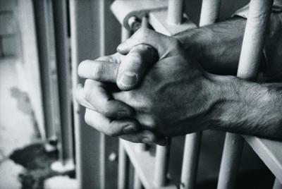 clasped hands, prison bars