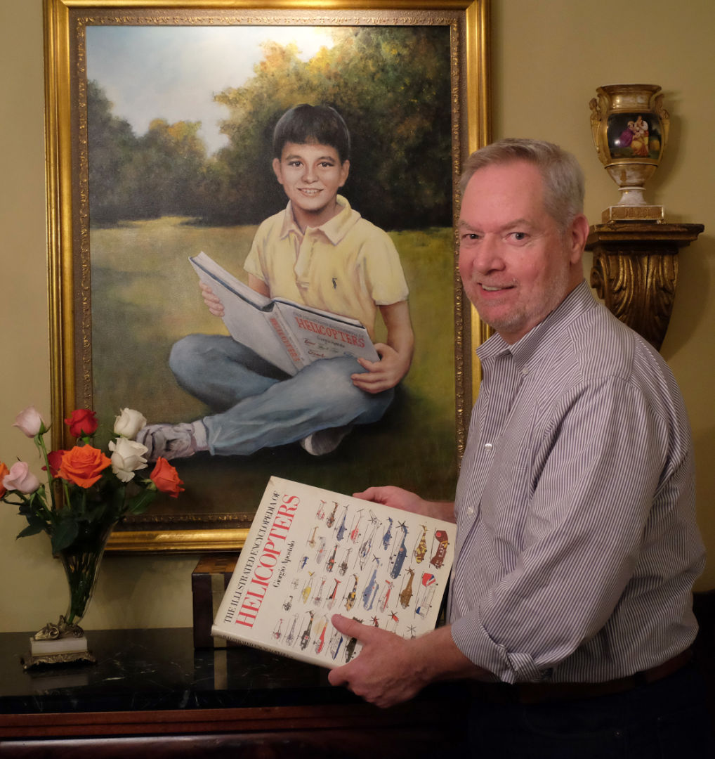Howard Wells holds a favorite book of his late son, Bage, shown in the Louis Briel painting