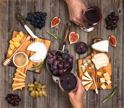 Flat-lay of couple or friends enjoying wine, eating and drinking together. Top view of people having party, celebrating at wooden rustic table. Cheese plate served with wine, grapes, fig and honey. Hands holding glasses.