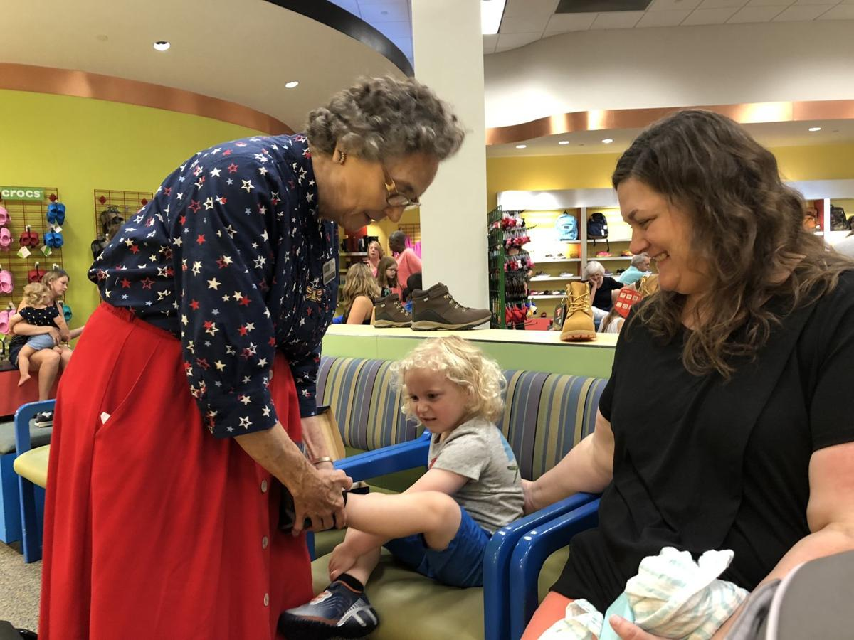 "2b753acd9673 Peggy Williams — ""Ms. Peggy"" to generations of customers — placed a pair of  shoes on Brody Kirby"