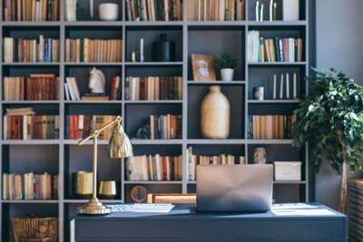 Table with laptop in home office interior.