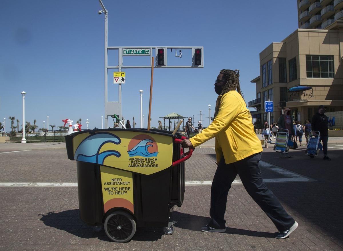 Lateeka Walker pushes a cleaning bin across the intersection of Atlantic Avenue and Laskin Road while working with the Virginia Beach Resort Area Ambassadors on Monday, April 5, 2021, in Virginia Beach, Va.