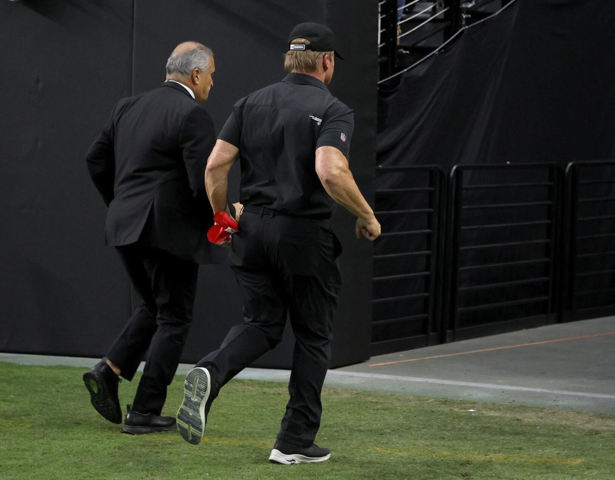 Las Vegas Raiders director of team security Bob Stiriti, left, and Raiders head coach Jon Gruden run off the field after the team's 20-9 loss to the Chicago Bears at Allegiant Stadium on Oct. 10, 2021, in Las Vegas.