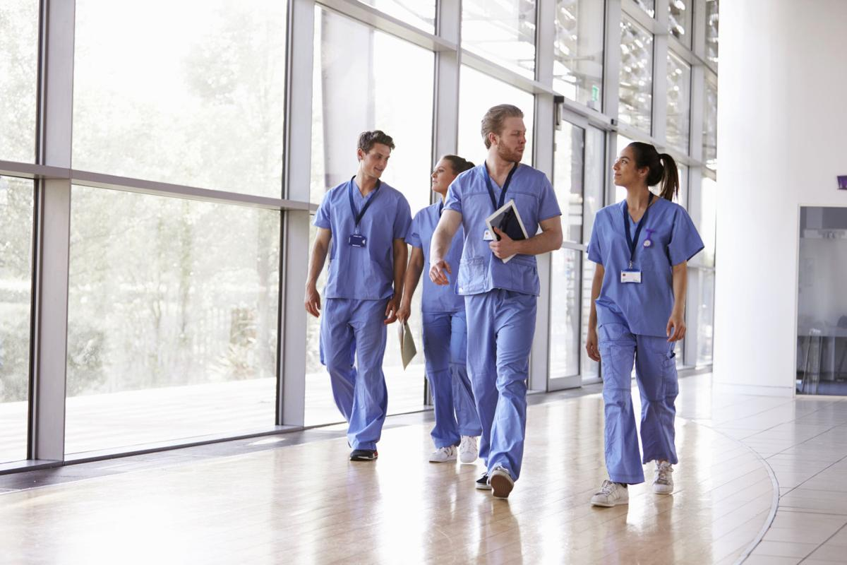 Four healthcare workers in scrubs