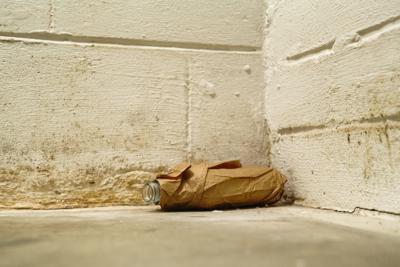 Floor level view of empty liquor bottle in brown bag