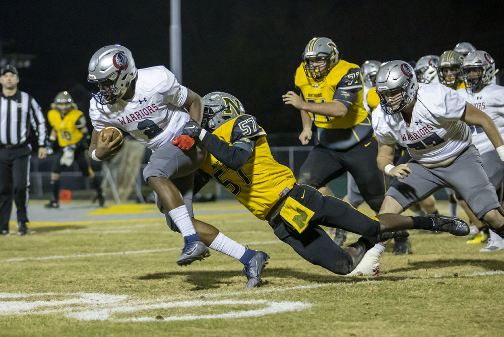 Northside's (57) Gavyn Preston tries to bring down Magna Vista's (2) Dryus Hairston. Northside's (71) Ethan Blank follows the play.