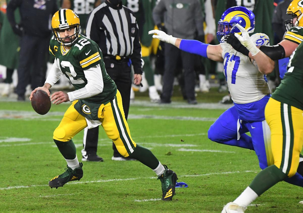 Green Bay Packers quarterback Aaron Rodgers looks for a receiver as Los Angeles Rams defensive lineman Morgan Fox pursues during an NFC Divisional playoff game at Lambeau Field in Green Bay, Wisconsin, on Saturday, Jan. 16, 2021.