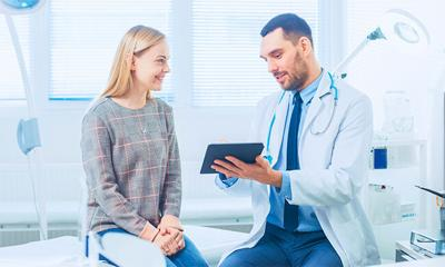 Beautiful Female Visits Doctor's Office, He Shows Tablet Computer with Her Medical History They Discuss Her Health and Other Medical Issues. Modern Medical Office.