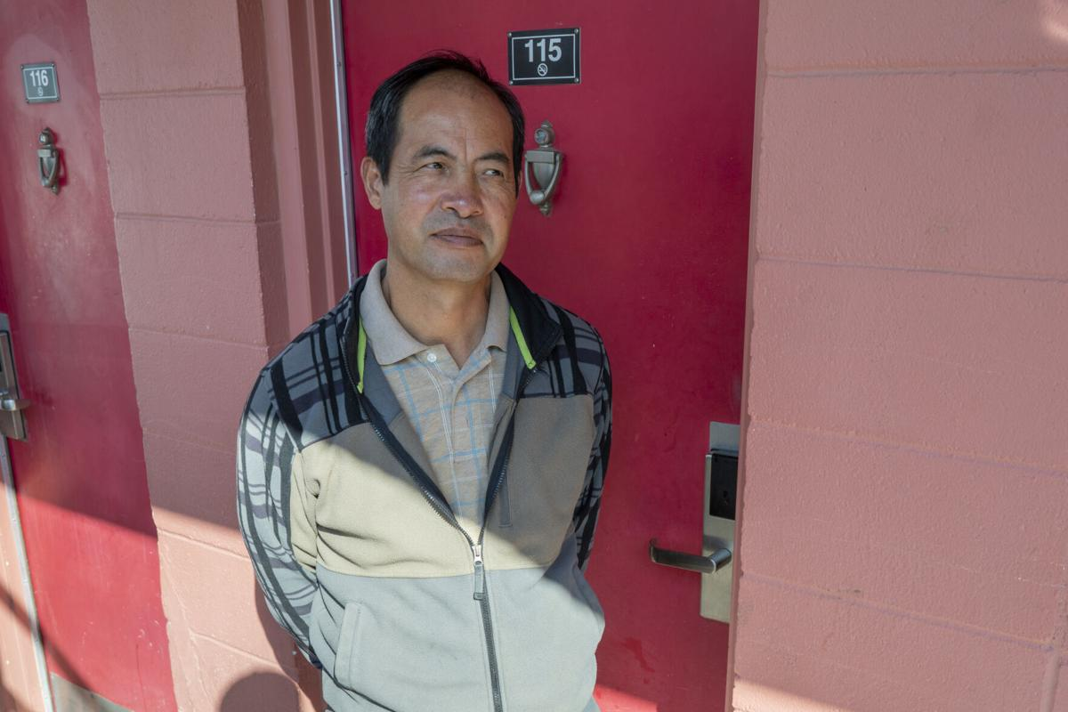 """Qinliang Wang in front of his room at a motel in Farmington, where he came to do what he thought was legal """"flower trimming"""" after being out of the workforce since March. Two days later, he was arrested in the room while pruning marijuana."""