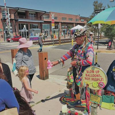 Santa Fe homeless advocate, clown made balloon animals for kids at Farmers Market