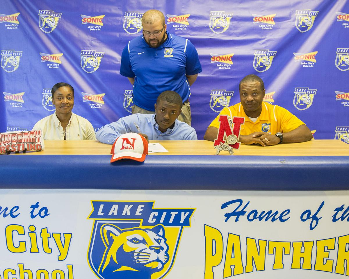Keenan graham center signs a national letter of intent to wrestle at newberry college also pictured are his parents jessica left and kevin right