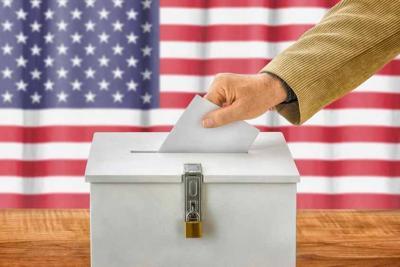 Man putting a ballot into a voting box - USA