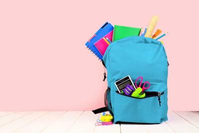 Blue backpack full of school supplies against a pink background. Back to school concept. Copy space.