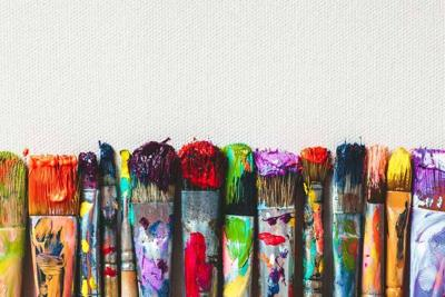 Row of artist paintbrushes closeup on artistic canvas.