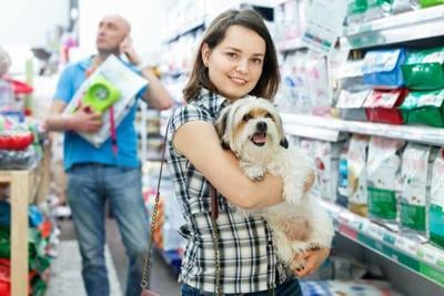 Young woman with dog in pet shop, during shopping with husband