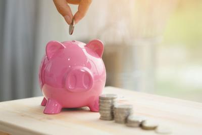 Little hand saving money in pink piggy bank