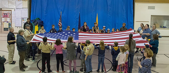Cub Scout Pack 327 folded the large American flag that the city flies during the Fourth of July on Tuesday night.