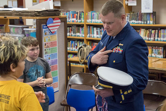 Chief Warrant Officer Shawn Erwin speaking with a student at Seward Elementary's annual veterans appreciation show on Friday.