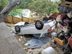 Car drives through carport wall, overturns on hillside below