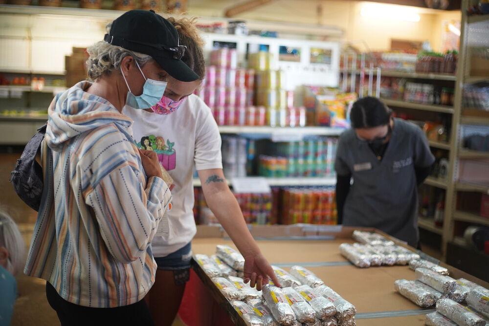 Customers, Elizabeth Woods and Kimberly Booker, look through the display of musubi at Takahashi Market in San Mateo.JPG