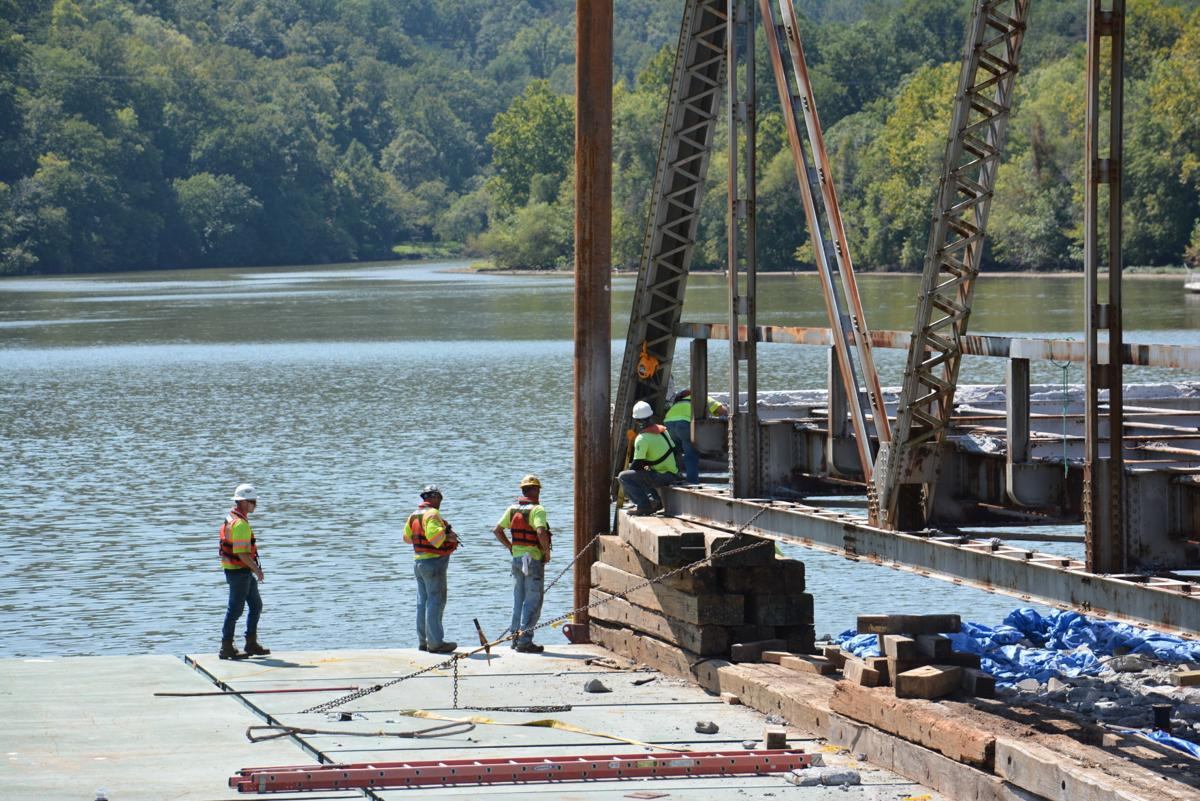 Workers remove old bridge piece by piece