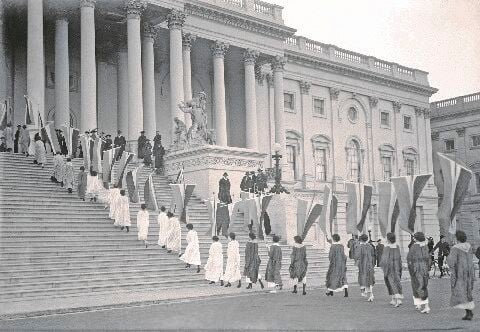 Woman suffrage demonstrators with banners at the U.S. Capitol in 1917. View of procession ascending Capitol steps.