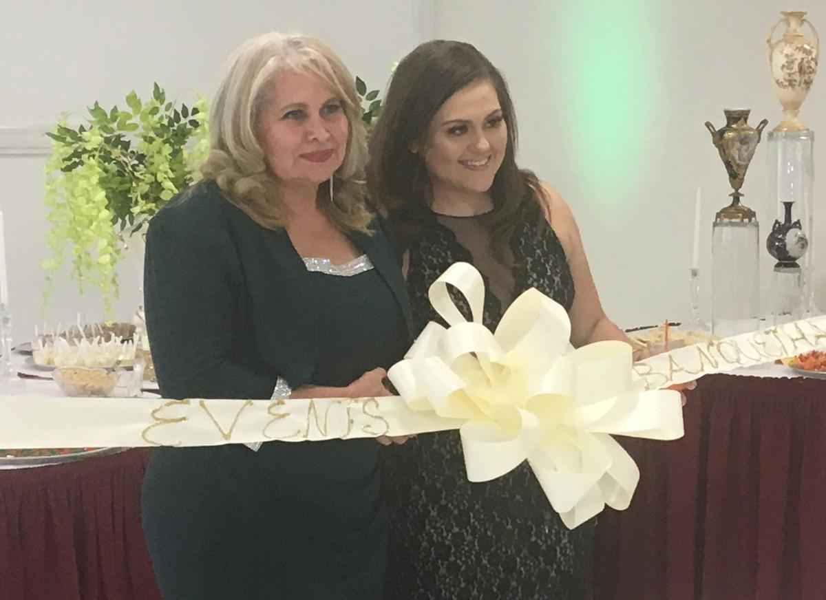 Olga Eby and her daughter officially open their new banquet hall by cuting the ribbon.