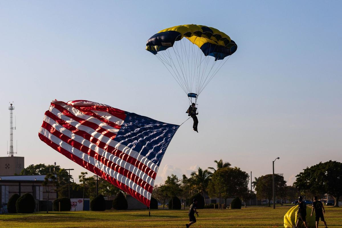 A member of the Leap Frogs Team comes in, trailed by Old Glory.