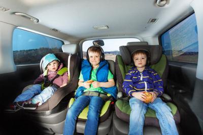 Three happy boys sitting in safety car seats