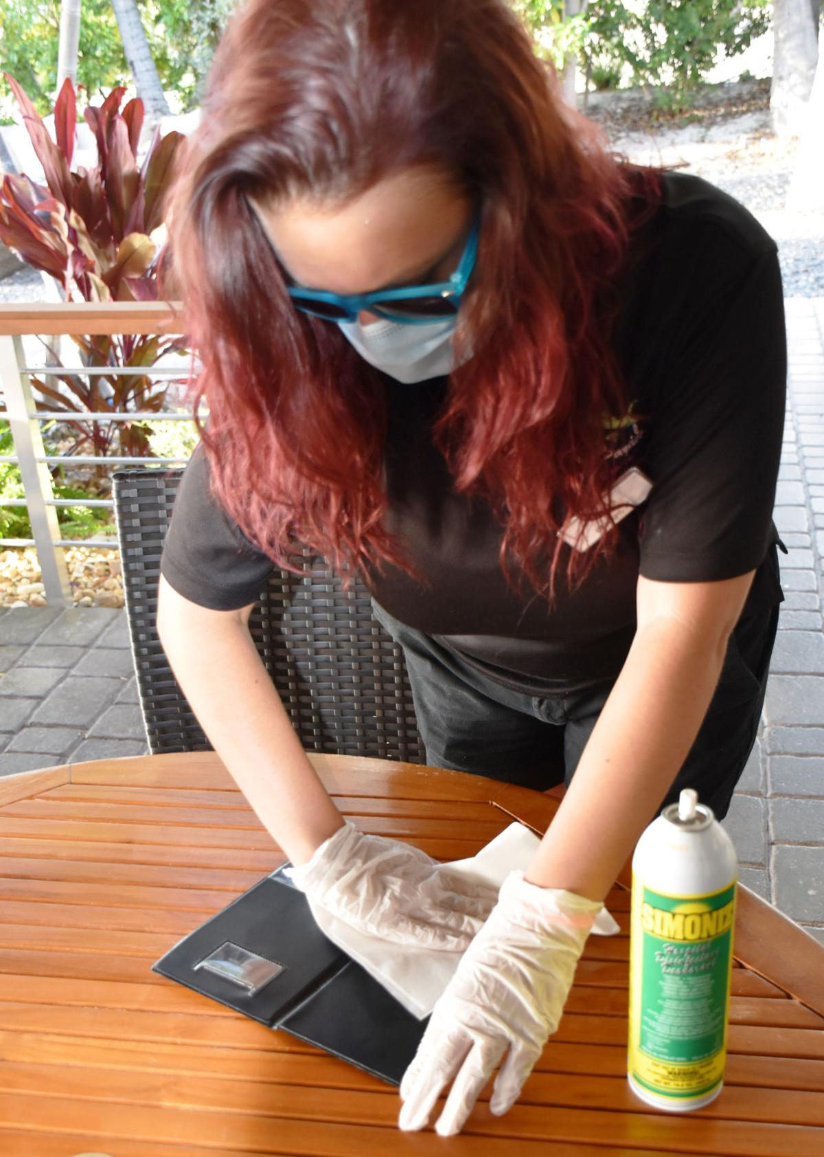 Staff at Snook's sanitize the restaurant's check holders after each use.