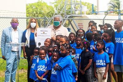 Tina Meadows Director, Grace Academy,  between her husband Pastor Mark Coates (Left) and  Florida City Mayor Otis Wallace (right) along with many smiling students.