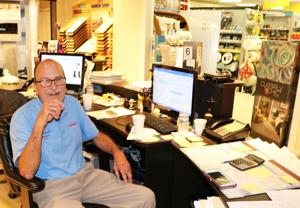 Curtis Mayes in his very busy, office hub at Berry's Paints.