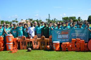 Coral Shores players and coaches are excited by new equipment donated by the Miami Dolphins and Baptist Health South Florida