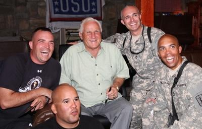 Former Miami Dolphins head coach Don Shula (center) poses for a photo with a group of service members at the Pat Tillman United Service Organizations, a building on Bagram Air Field, July 15, during a celebrity visit to Afghanistan.