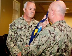 Rear Adm. Collin P. Green, outgoing commander for Special Operations Command South, hands the unit guidon signifying relinquishing of command to Adm. Kurt W. Tidd, U.S. Southern Command Commander, during a change of command ceremony at Homestead Air Reserve Base, Fla, June 5, 2018. The passing of the unit colors to U.S. Navy Adm. Kurt W. Tidd signifies that the unit is never without leadership.