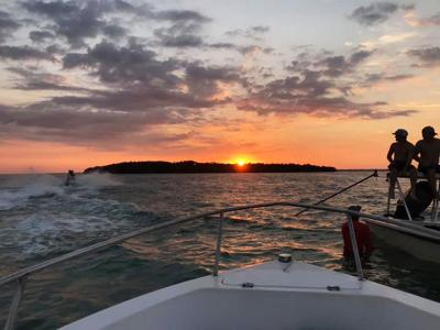 Local Upper Keys residents Matthew Mitjans, Bryce Wheaton, and AJ Juliano enjoy the sunset after a long day of fishing.